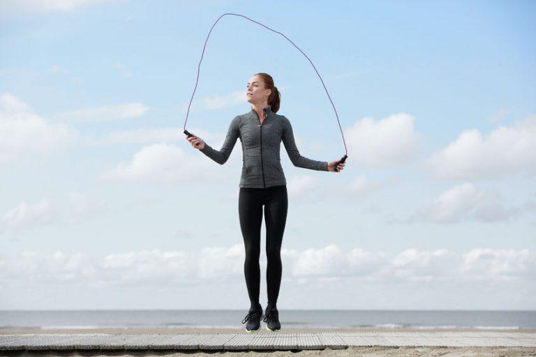 Donna che salta la corda sul lungo mare