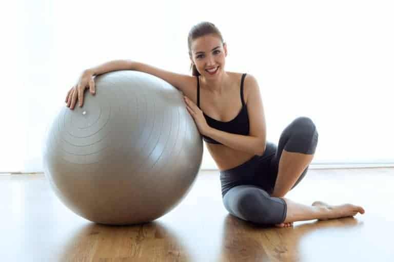Donna con palla per pilates grigia