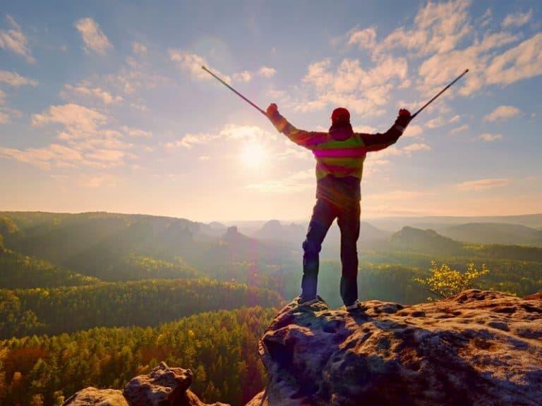 Uomo che esulta con i bastoncini da trekking