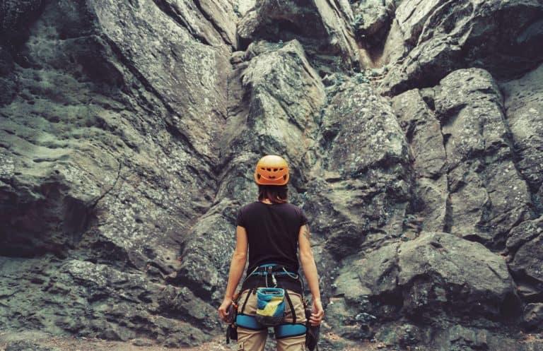 Donna davanti a una parete da scalare