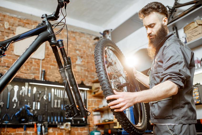 Uomo con in mano una ruota di bicicletta