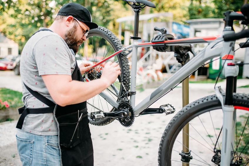Persona che aggiusta la ruota di una bicicletta