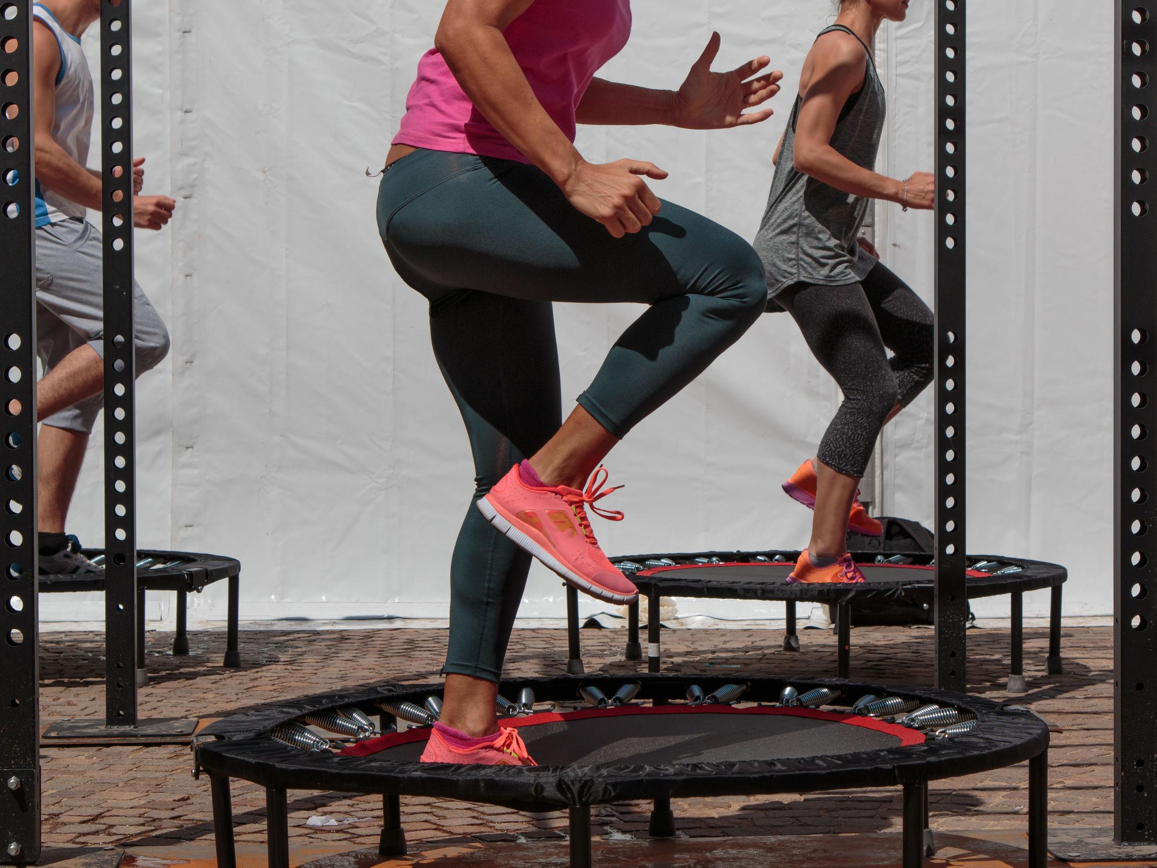 Entrenamiento de mini trampolín: Chica haciendo ejercicio físico en clase en el gimnasio