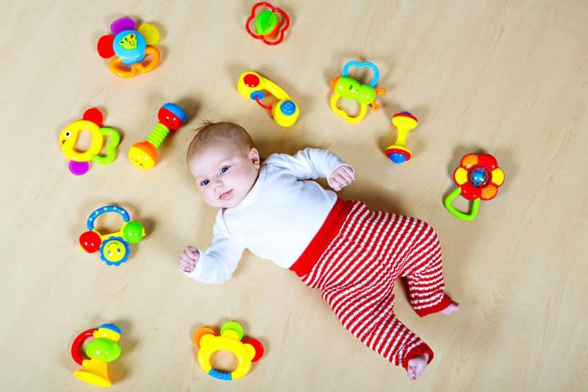 Bebê deitado no chão com diversos chocalhos ao redor.