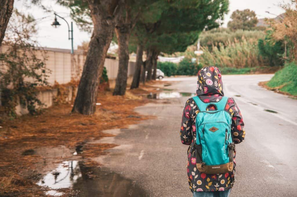 Mulher na rua com capa de chuva e mochila.