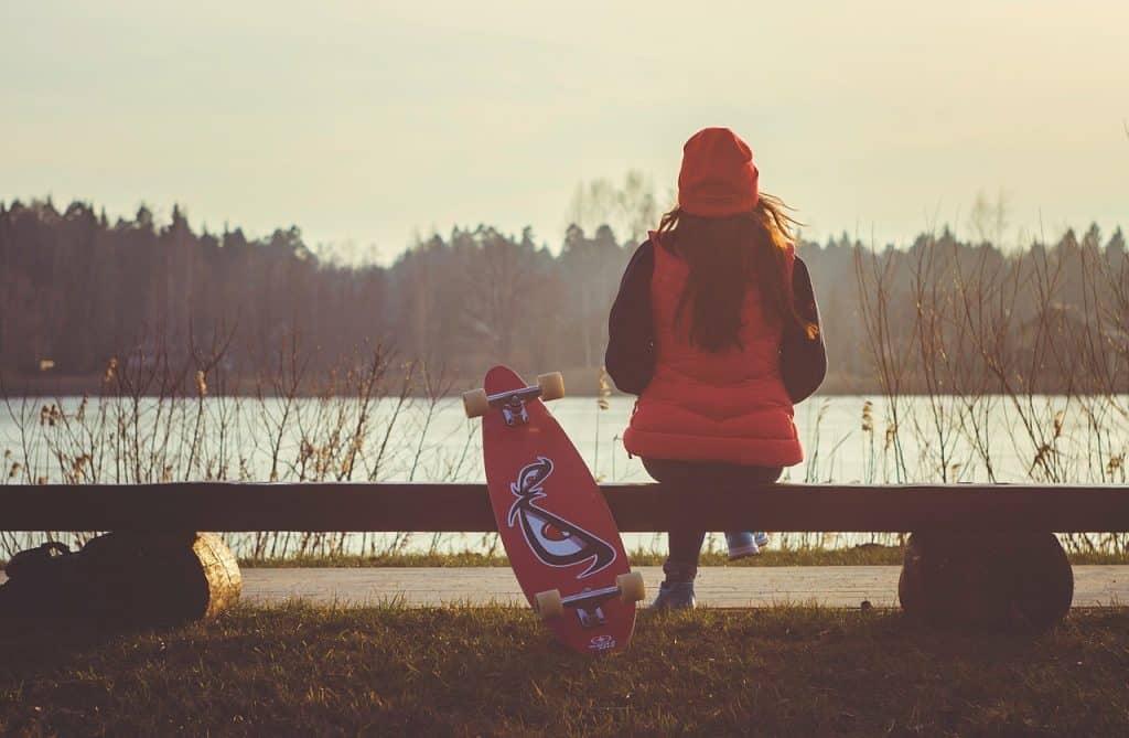 Com um skate ao lado, garota sentada em um banco à beira de um lago observa a natureza.