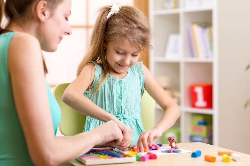 Mãe e filha brincando com massinha em mesa infantil.