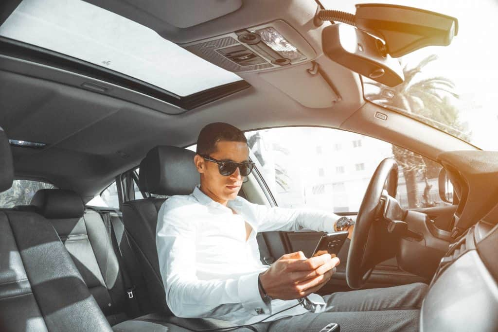 Homem dentro de um carro, mexendo em um celular conectado ao carregador