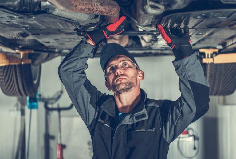 Imagem mostra um mecânico trabalhando em um automóvel.