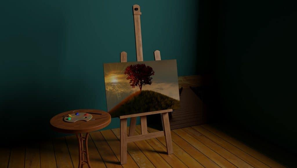 A imagem mostra um quadro em destaque com uma pintura de uma montanha com uma árvore no topo e o sol ao lado. O quadro está num cavalete de madeira e tem uma mesinha na lateral esquerda com pincel e tinta.
