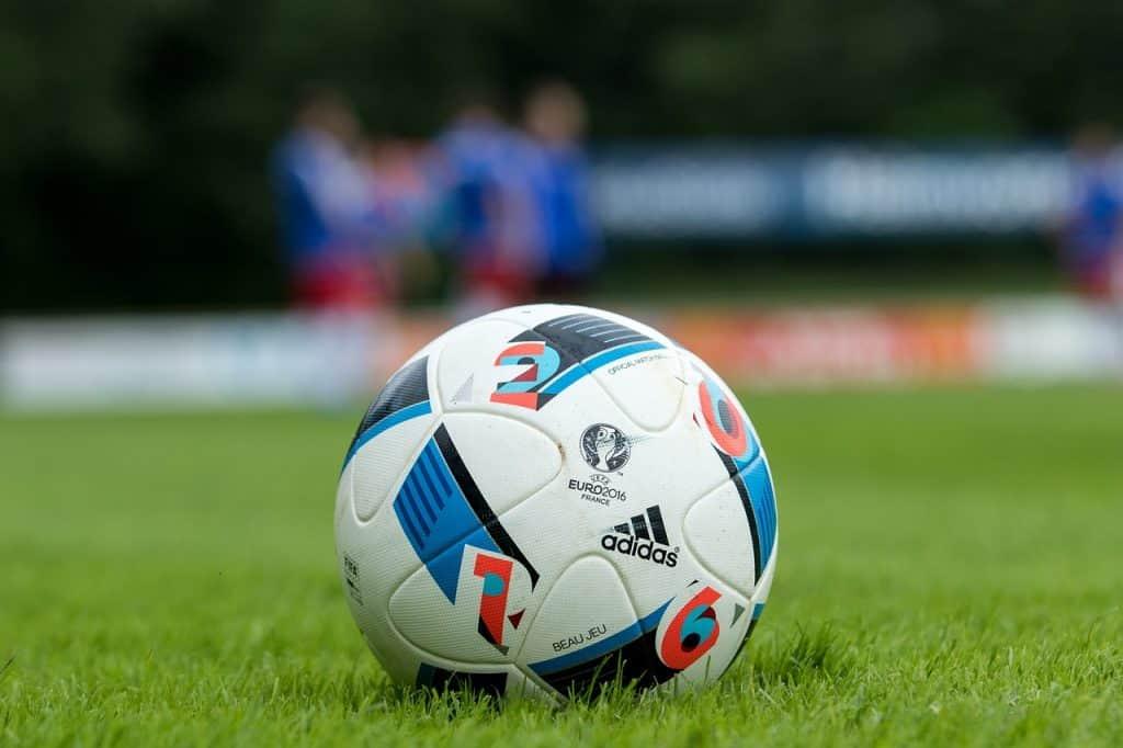 Imagem de bola de futebol adidas sobre gramado.