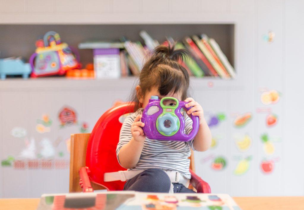 Na foto uma menina brincando com uma câmera de brinquedo.