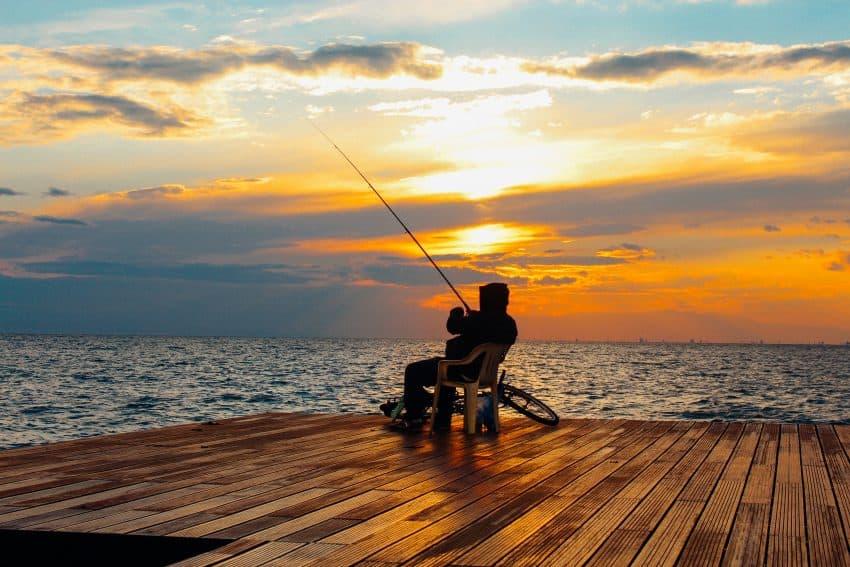 Homem pescando sentado em uma cadeira de plástico.