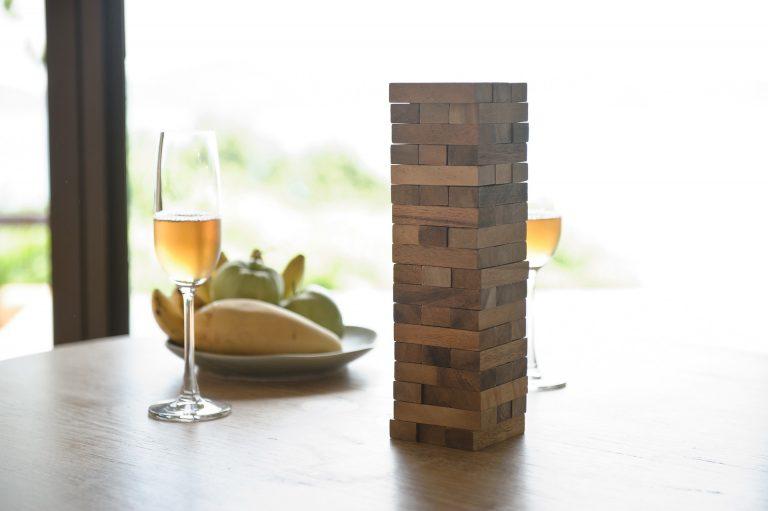 Uma torre de jenga ao lado de dois copos com vinho branco e de algumas frutas em um prato. Tudo está sobre uma mesa de madeira.