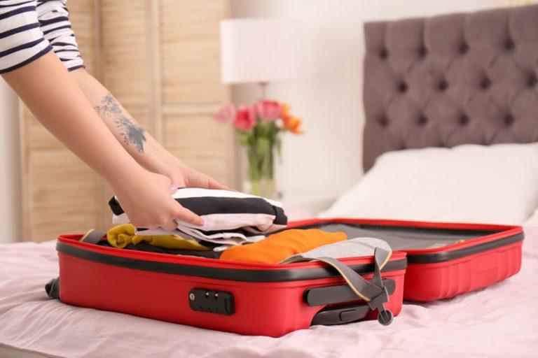 Pessoa guardando pertences dentro da mala.