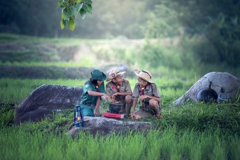 Três escoteiros usando um pequeno fogão para cozinhar no meio da selva