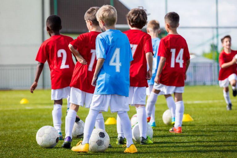 Imagem mostra um grupo de crianças treinando futebol em um campo com chapéus chineses.