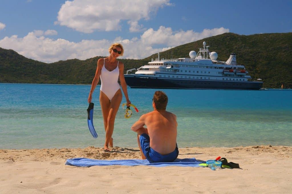 Na foto um homem e uma mulher em uma praia com um navio ao fundo.