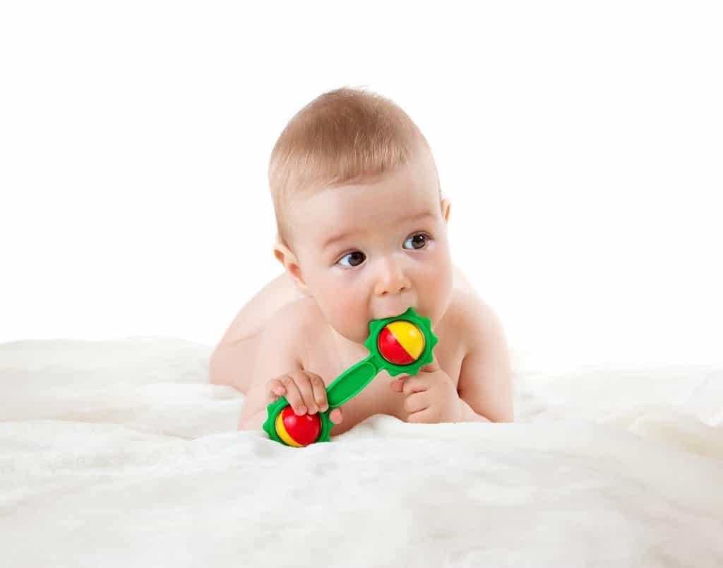 Bebê deitado de bruços com um chocalho na mão.