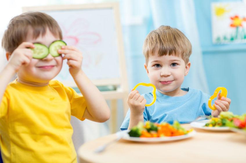 Dois meninos comendo em uma mesinha infantil.
