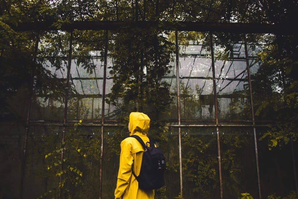 Pessoa de capa de chuva e mochila.