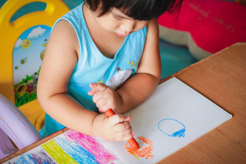 Imagem de uma menina sentada em sua mesinha infantil usando giz de cera.