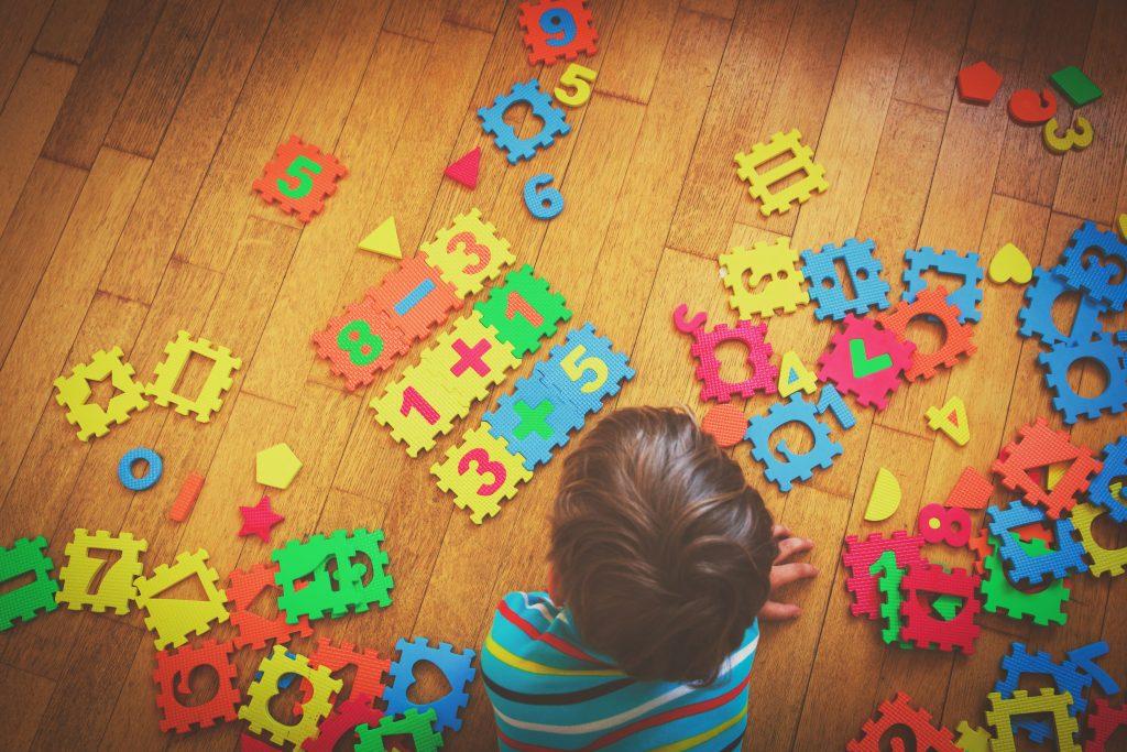 Peças com letras e números e criança brincando.