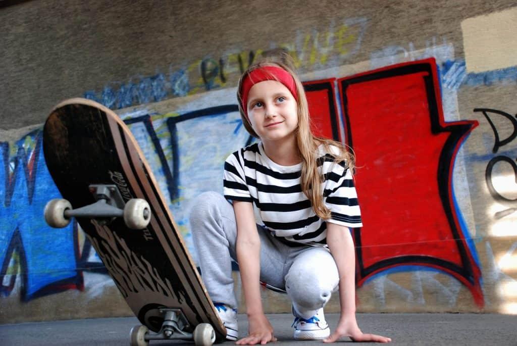 Imagem mostra uma menina agachada com um dos pés sobre um skate.