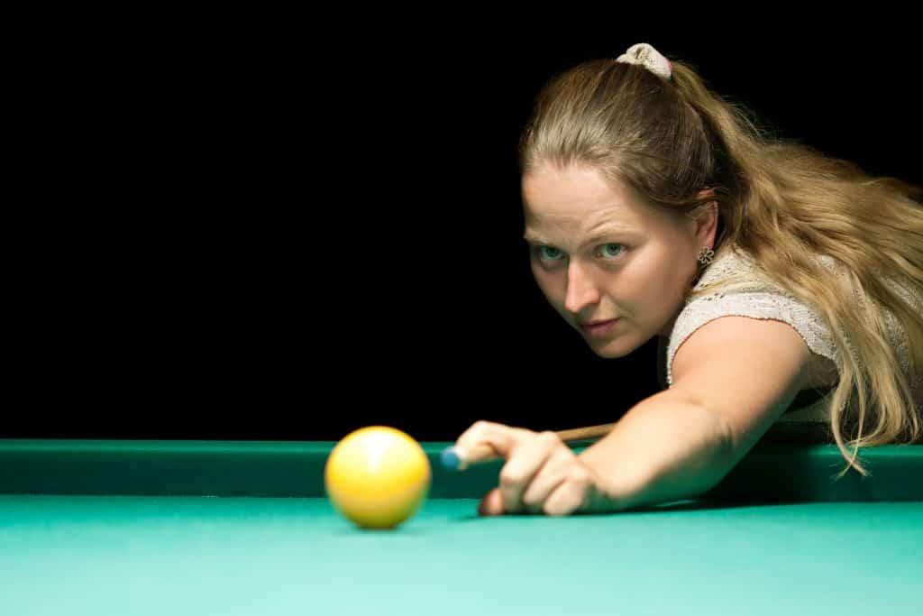 Imagem de uma mulher concentrada antes de realizar uma tacada de sinuca.