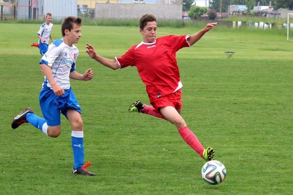Dois jovens jogadores em destaque e um deles preparando-se para chutar uma bola de futebol Adidas.