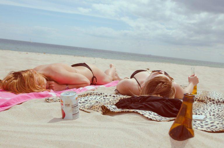 Imagem de mulheres deitadas na praia tomando cerveja
