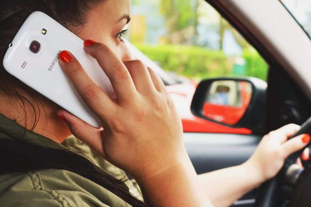 Mulher falando em um telefone celular dentro de carro.