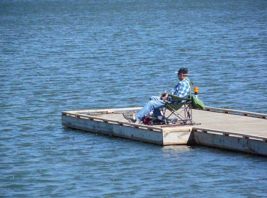 Senhor pescando em trapiche sentado em sua cadeira de pesca.