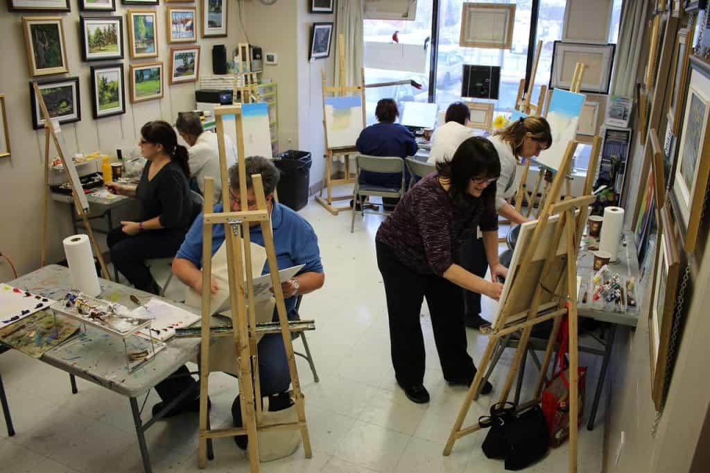 Imagem de atelier de pintura com pintores e seus quadros em cavalete.