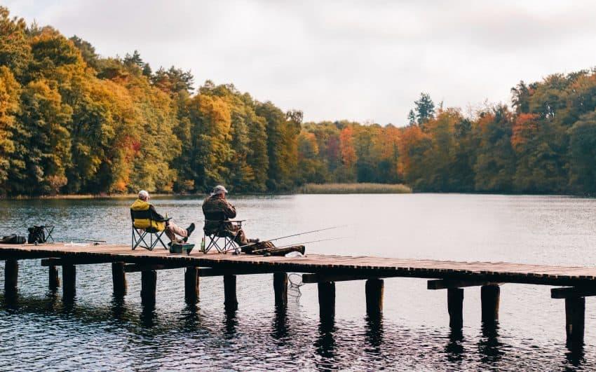 Dois homens pescando em um lado sentados em cadeiras de pesca.