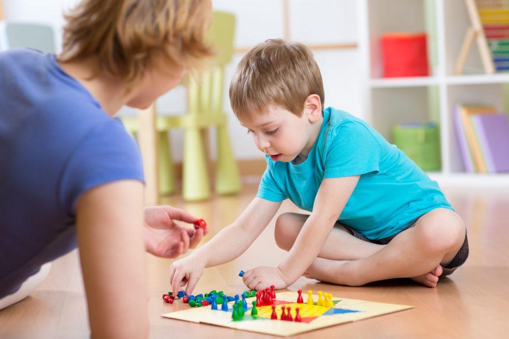 Mãe e filho brincando de ludo no chão.