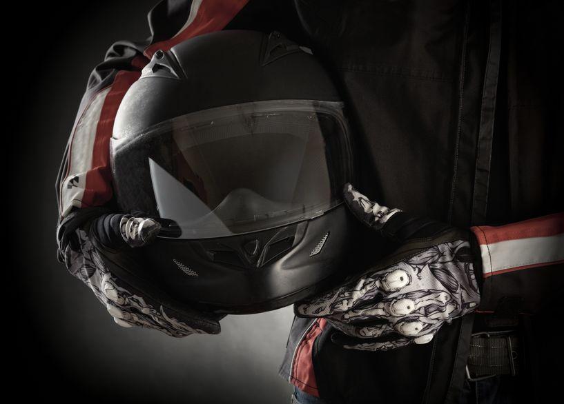 Um homem vestido com roupa de moto segurando um capacete.